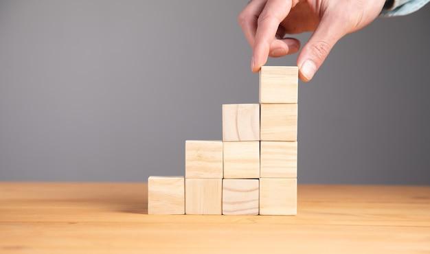 Segurando cubos de blocos de madeira em branco no fundo da mesa, fundo de conceito de negócio