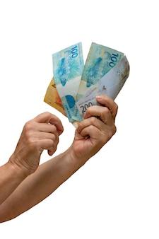 Segurando dinheiro real brasileiro, notas de 200, 100, 50 e 20 isoladas em parede branca. espaço para texto.