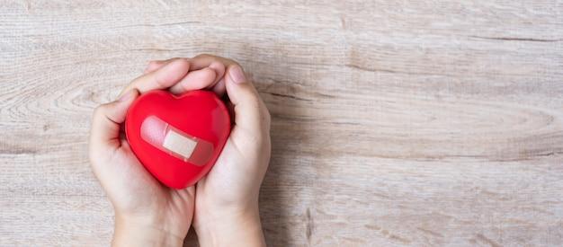 Segurando forma de coração vermelho sobre fundo de madeira. cuidados de saúde