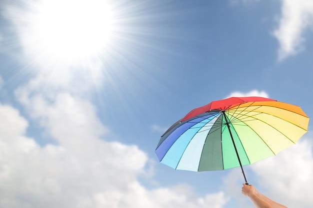 Segurando guarda-chuva colorido para proteção contra a luz ultravioleta.
