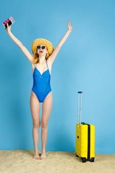 Segurando ingressos. mulher jovem feliz com bolsa preparada para viajar no fundo azul do estúdio. conceito de emoções humanas, expressão facial, férias de verão, fim de semana. verão, mar, oceano, álcool.