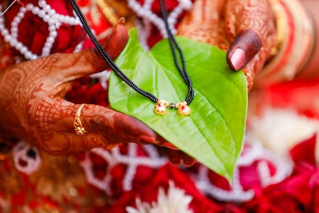 Segurando mangalsutra na mão da noiva o símbolo do casamento no hinduísmo