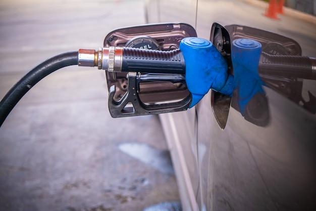 Segurando o bico de combustível azul para reabastecer a gasolina para o carro