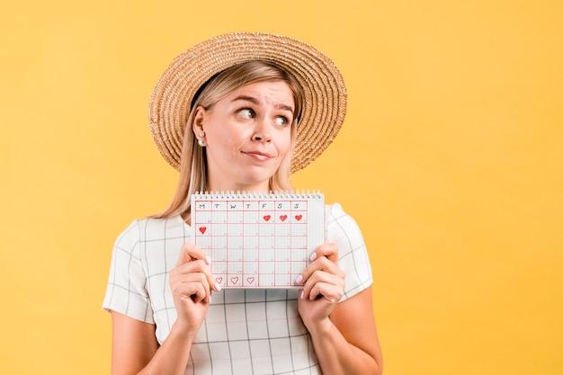 Segurando o calendário do período e desviando o olhar da mulher