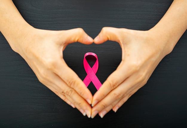 Segurando o conceito de câncer de fita rosa para o símbolo do show.