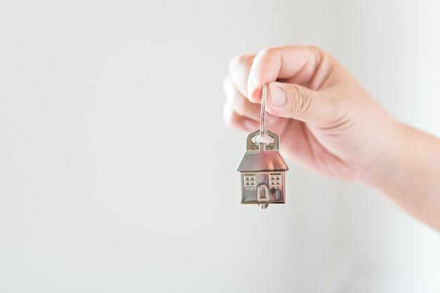 Segurando o conceito de chaves de casa, chaves de casa para casa nova, compra de casa nova