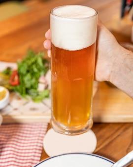 Segurando o copo de caneca de cerveja, lugar vazio para logotipo, nome
