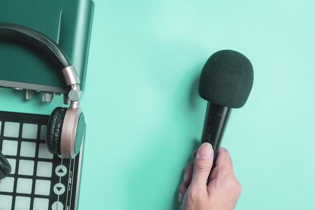 Segurando o microfone e fone de ouvido de interface de música em azul