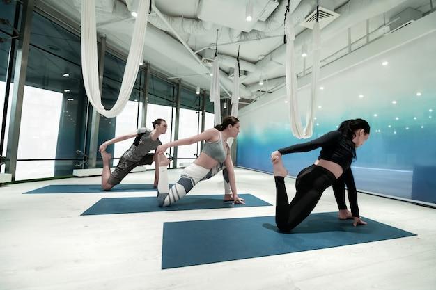 Segurando o pé. duas mulheres em forma e magras e um homem segurando seus pés enquanto se alongam fazendo ioga