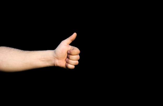 Segurando o polegar com um sinal semelhante. isolado em um fundo preto.
