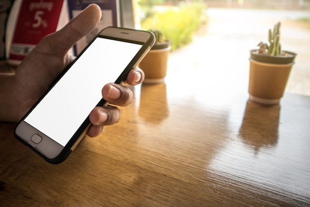 Segurando o telefone celular e jogar aplicativo no café