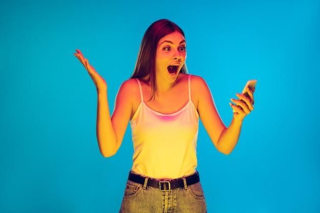 Segurando o telefone, louco feliz vencedor chocado retrato de uma mulher caucasiana em azul