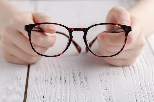 Segurando os óculos nas mãos femininas