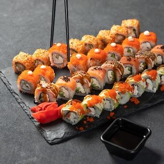 Segurando sushi com pauzinho. feng shui roll, kani hot sushi roll com philadelphia roll close up