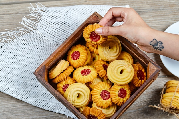 Segurando um biscoito e uma cesta de biscoitos variados na mesa de madeira.