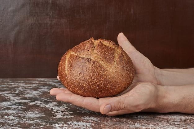 Segurando um bolo de pão na mão.