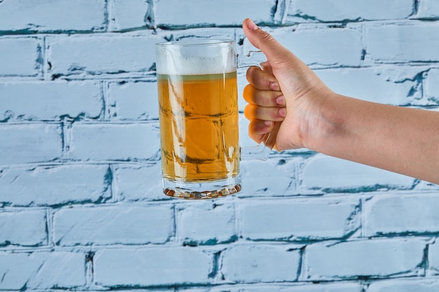 Segurando um copo de cerveja em um fundo azul.