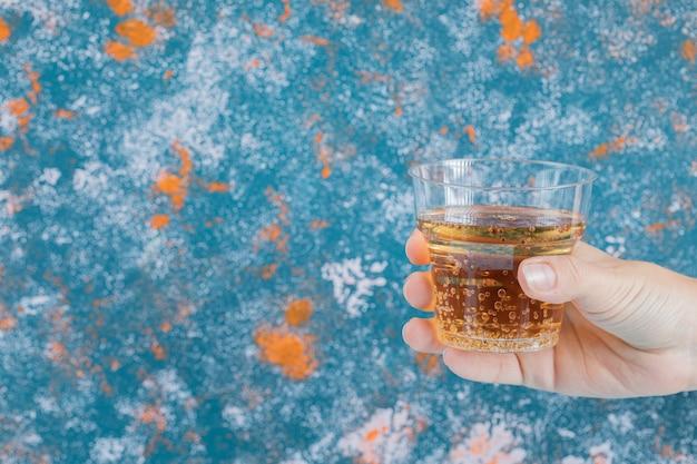 Segurando um copo de plástico com bebida amarela