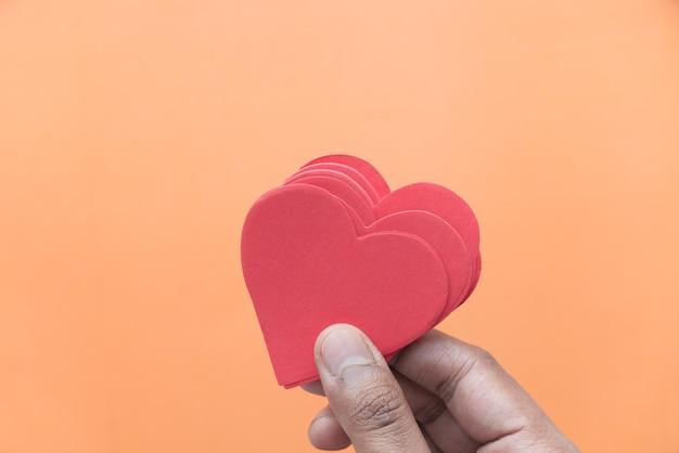 Segurando um coração vermelho em um fundo laranja de cima para baixo