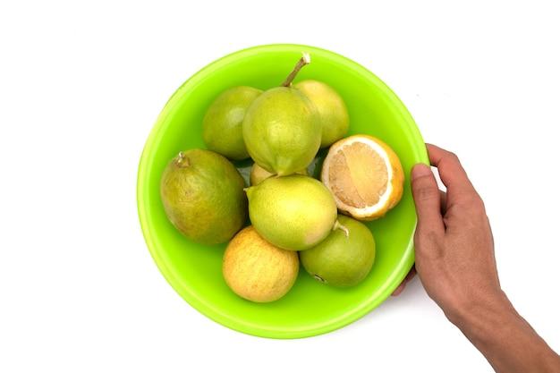Segurando um limão em um prato em um fundo branco