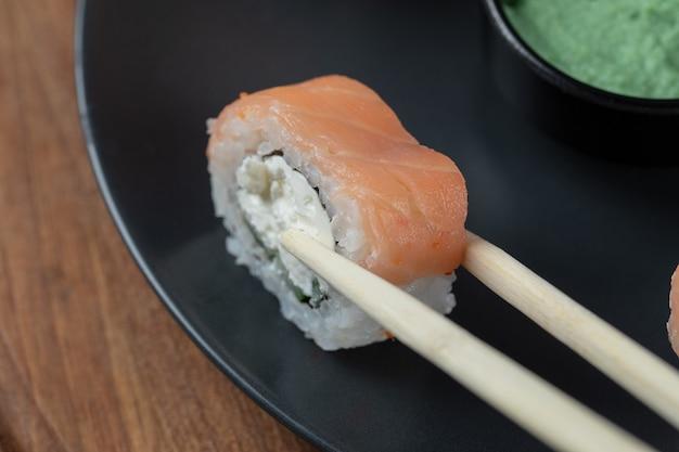 Segurando um rolo de sushi de salmão com pauzinhos.