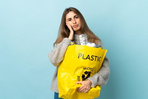 Segurando um saco cheio de garrafas de plástico para reciclar sobre azul isolado infeliz e frustrado