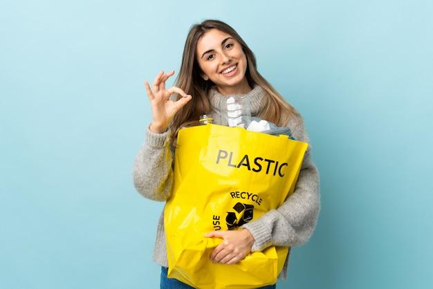 Segurando um saco cheio de garrafas de plástico para reciclar sobre azul isolado, mostrando um sinal de ok com os dedos