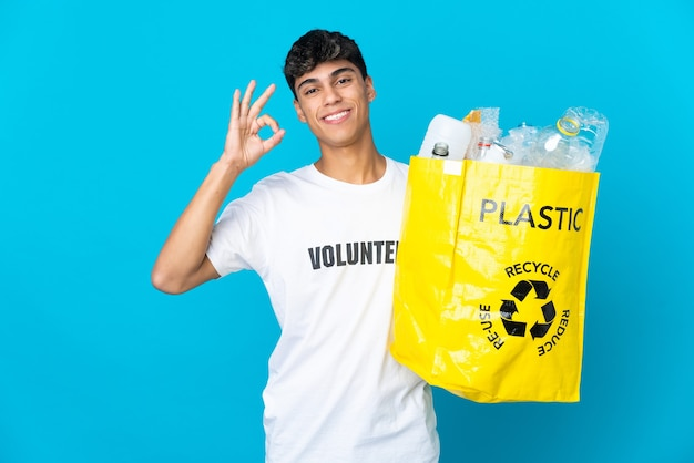 Segurando um saco cheio de garrafas de plástico para reciclar sobre o azul, mostrando o sinal de ok com os dedos