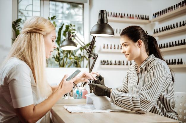 Segurando um smartphone. mulher loira segurando seu smartphone sentada na frente de uma jovem artista experiente de unhas