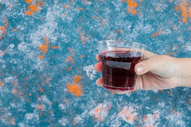 Segurando um suco vermelho em um copo de plástico