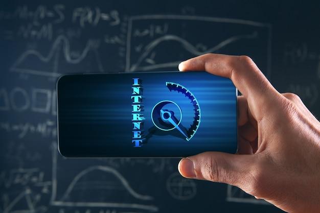 Segurando um telefone com um sensor de velocidade da internet em um fundo de quadro branco