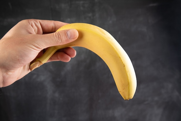 Segurando uma banana amarela em uma superfície escura