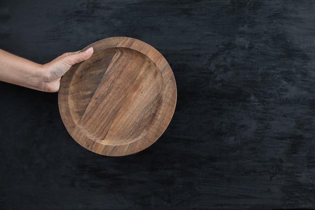 Segurando uma bandeja de madeira circular com a mão