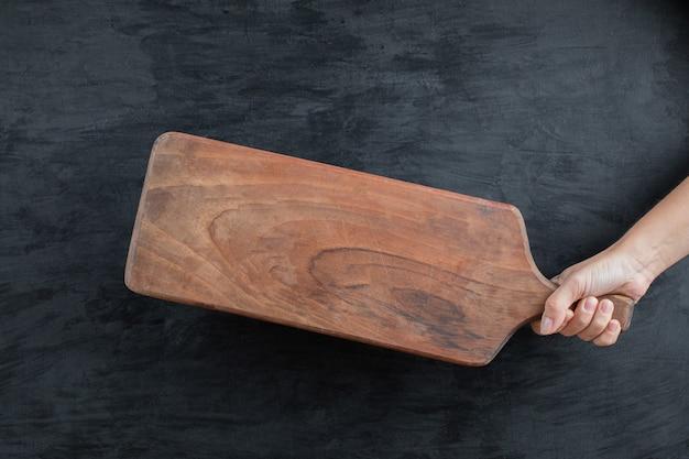 Segurando uma bandeja de madeira na mão sobre fundo preto
