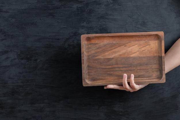 Segurando uma bandeja quadrada de madeira com a mão