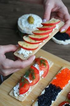 Segurando uma bolacha vegana com fatias de maçã e queijo ricota. biscoitos misturados na placa de madeira.