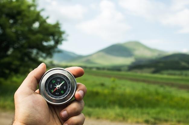 Segurando uma bússola contra o fundo de um campo verde durante o dia