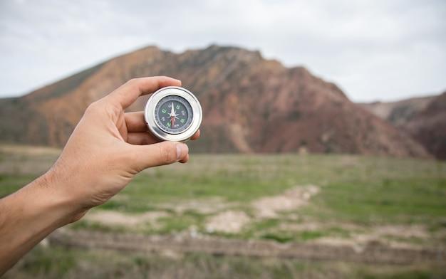 Segurando uma bússola na superfície de uma montanha avermelhada