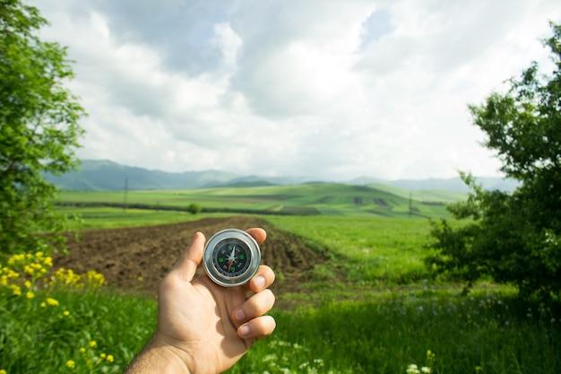 Segurando uma bússola no fundo dos campos
