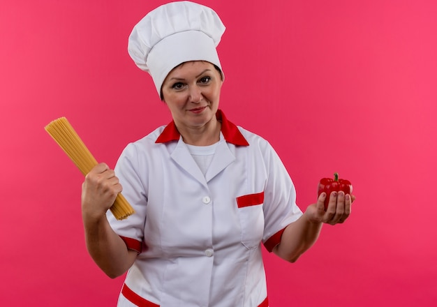 Segurando uma cozinheira de meia-idade em uniforme de chef segurando espaguete e pimenta na parede rosa isolada
