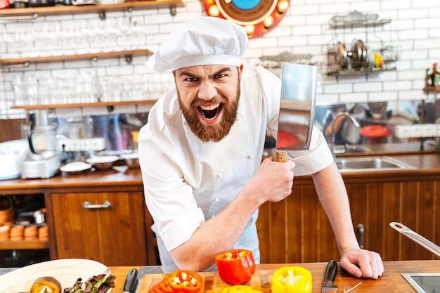 Segurando uma faca de cutelo e gritando na cozinha
