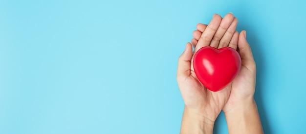 Segurando uma forma de coração vermelho sobre fundo azul