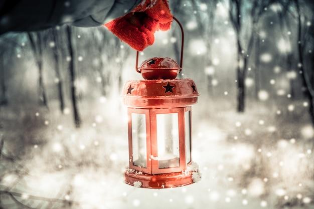 Segurando uma lanterna de vela vermelha na floresta de inverno