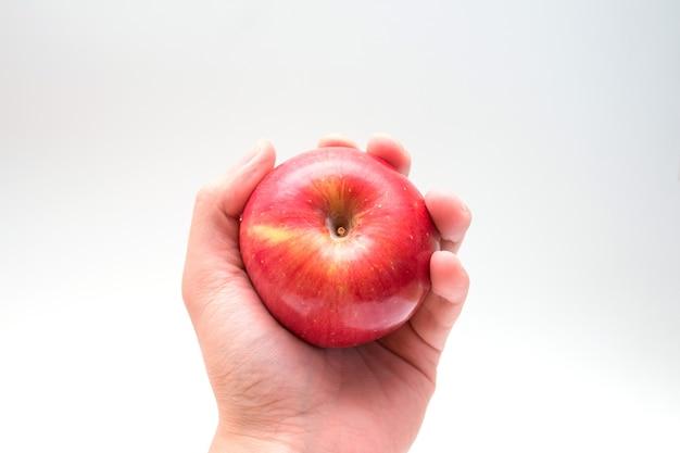 Segurando uma maçã na mão por baixo, isolada no fundo branco