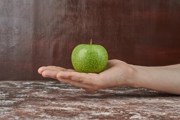 Segurando uma maçã verde na mão.