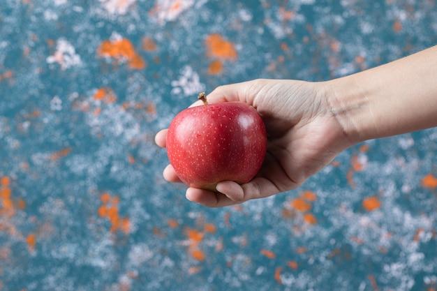 Segurando uma maçã vermelha na mão na superfície azul