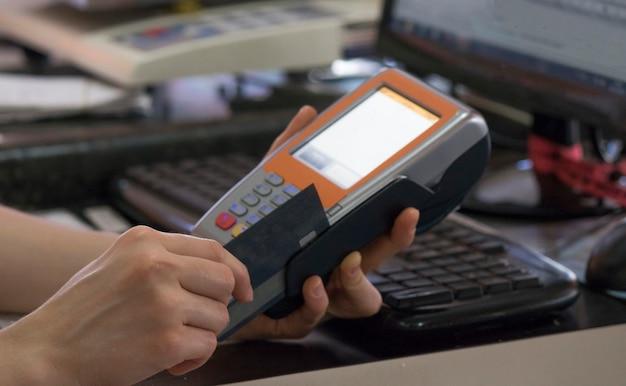 Segurando uma máquina de furto de pagamento com cartão de crédito em um restaurante