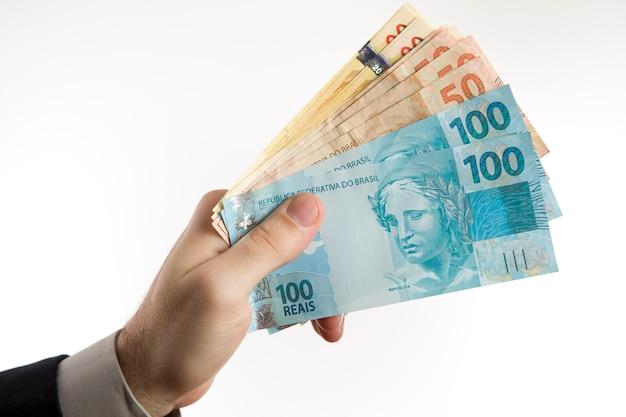 Segurando uma moeda brasileira.