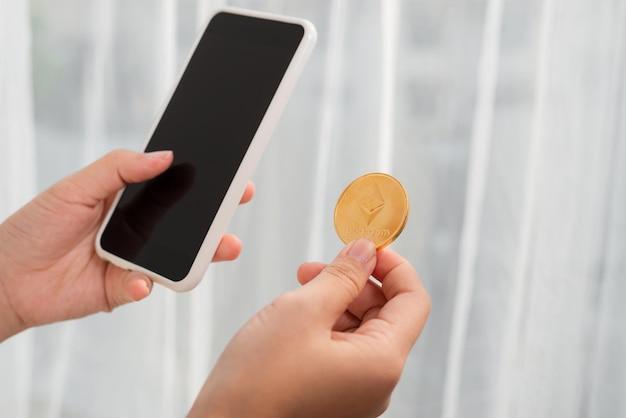Segurando uma moeda criptográfica e um telefone celular no fundo branco