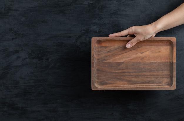 Segurando uma placa quadrada de madeira em fundo preto